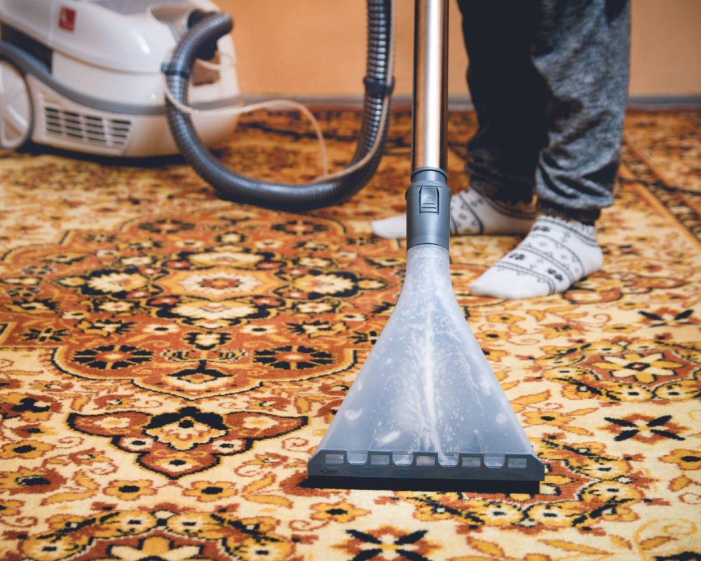 Woman cleaning persian carpet by washing hoover