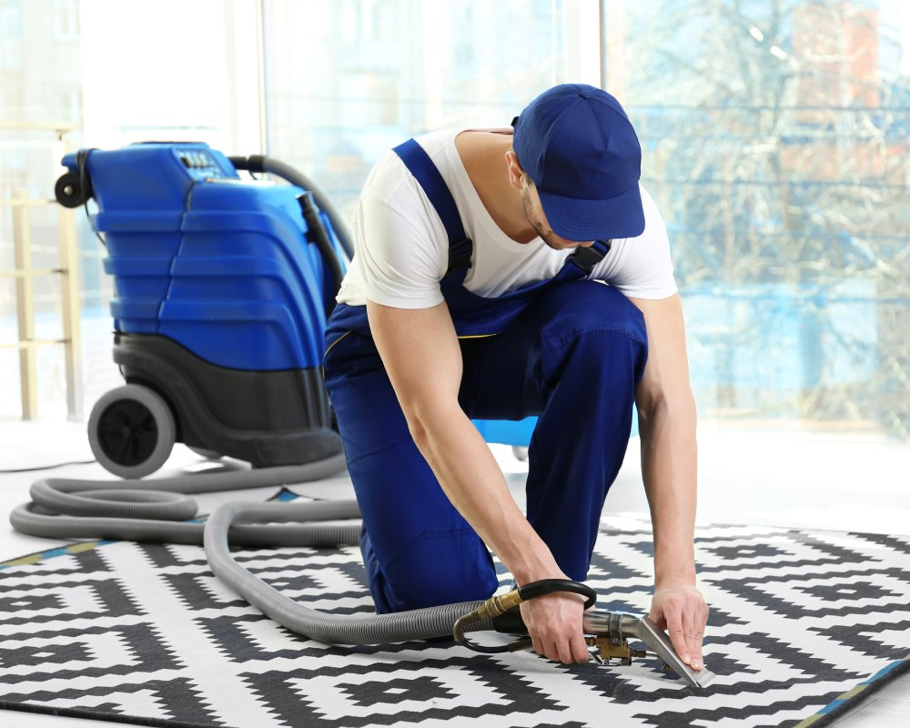 Man cleaning carpet with vacuum cleaner, closeup.